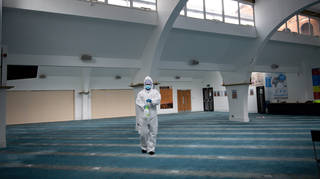 A staff member at Green Lane Mosque in Birmingham disinfects prayer rooms, ahead of Eid al-Fitr