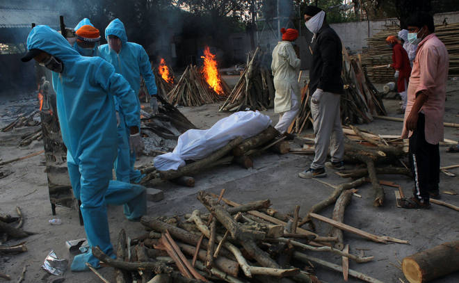 Family members in PPE prepare the body a Covid-19 victim for cremation in New Delhi, India