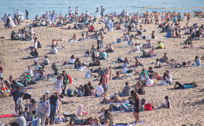 A crowd of people seen on the beach of Barceloneta in Barcelona, Spain