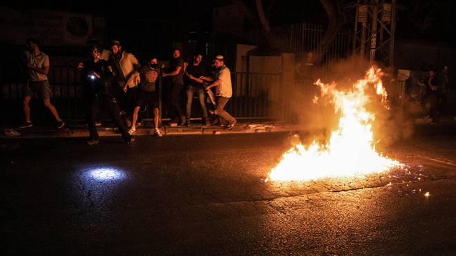 Molotov cocktails are thrown at Jewish right-wing protesters during clashes in the Israeli city of oLd