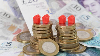 Models of houses on top of coins and banknotes