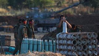An Israeli soldier arms artillery shells next to an artillery unit at the Israeli-Gaza border