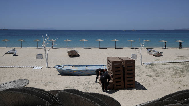 Workers arrange sunbeds as others install umbrellas at Plaka beach on the Aegean island of Naxos, Greece