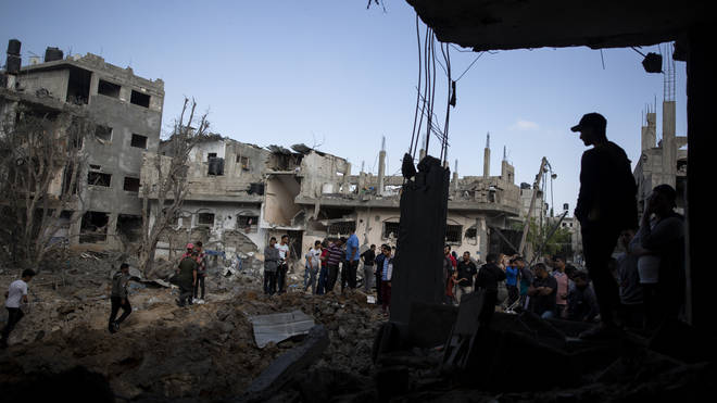 Palestinians inspect their destroyed houses following overnight Israeli air strikes in town of Beit Hanoun, northern Gaza Strip