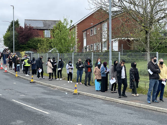 People queue for the vaccination centre at the Essa Academy in Bolton.