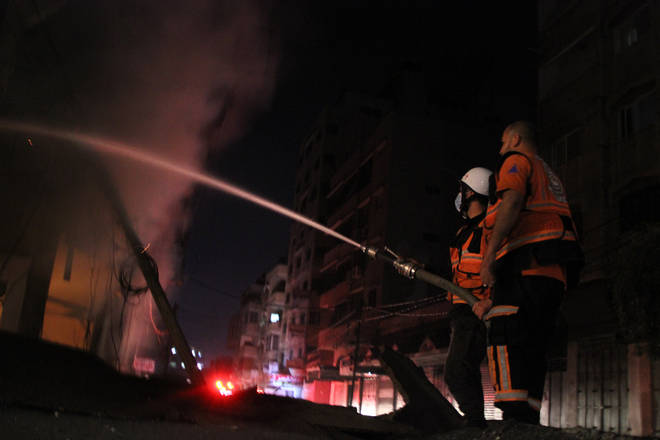 Firefighters attempt to extinguish flames after a Israeli airstrike in Gaza City.