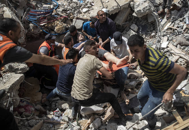 Palestinians rescue a survivor from under the rubble of a destroyed residential building following deadly Israeli airstrikes in Gaza on Sunday.