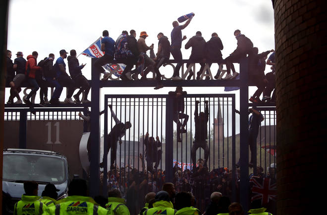 Rangers fans sit on the gate outside the ground during the Scottish Premiership match at Ibrox Stadium.