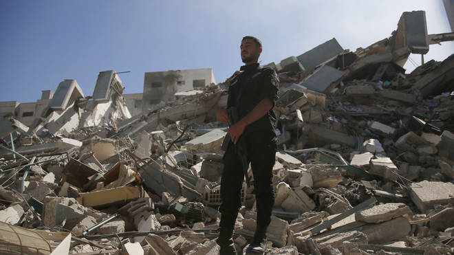 A policeman stands in the rubble of the building that housed The Associated Press offices in Gaza City
