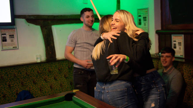 Friends hug for the first time in months inside the Oak Inn in Coventry