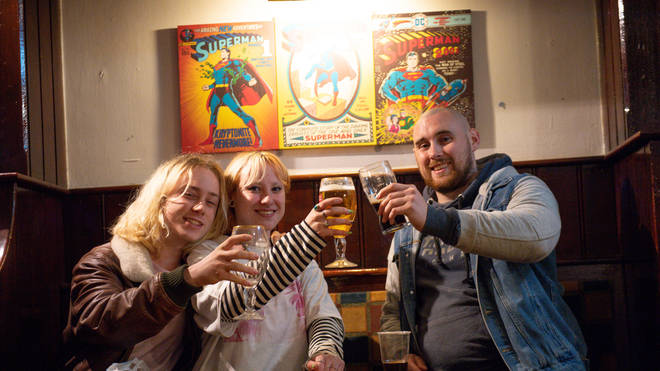 Punters raise a glass together inside a pub for the first time in months