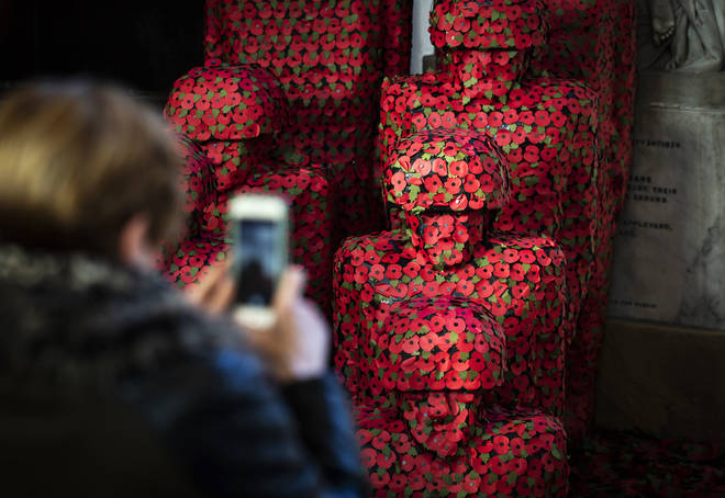 A woman Takes A Photograph Of An Installation Titled Coming Home By Artist Martin Waters at Hull Minster