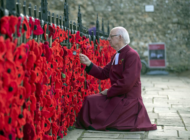 Canon Nick Fennemore, Chaplain of Winchester Cathedral Looks At The Woollen Poppies Have Been Hung On The Railings Outside The Cathedral In Hampshire To Recall The Poppy Fields Of Flanders