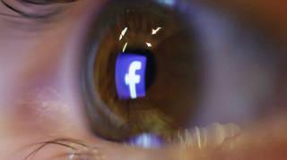 The Facebook logo reflected in an eye