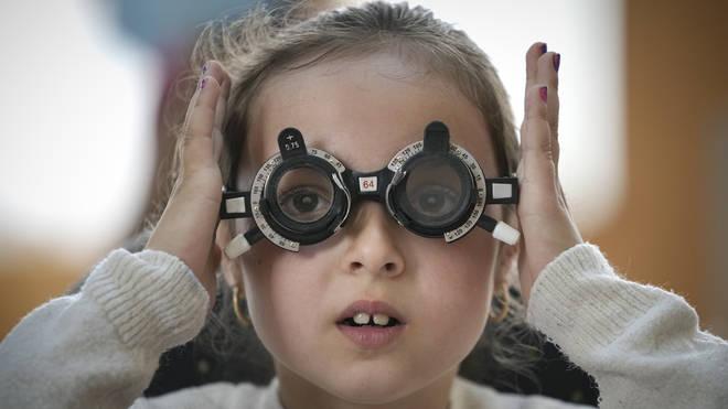 A little girl adjusts testing glasses during an eyesight examination (Vadim Ghirda/AP)
