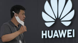 A worker waits for customers inside a Huawei store in Beijing
