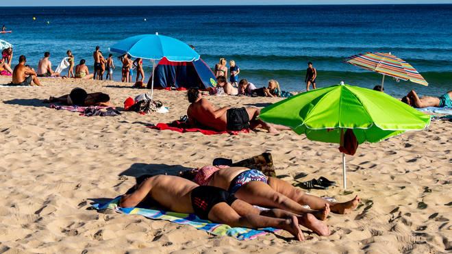 Tourists enjoy Porto de Mos Beach in Lagos, Portugal