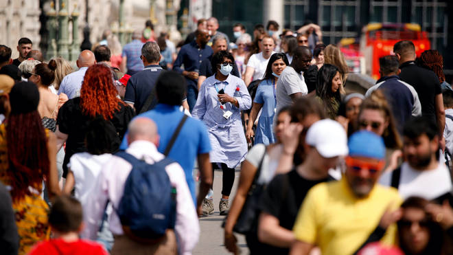A woman wearing a face mask crosses a busy Westminster Bridge in London