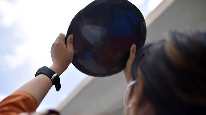 Nepalese people observing a partial solar eclipse using a solar filter