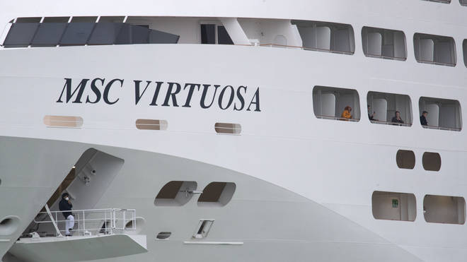 Passengers look out from the side of the cruise ship MSC Virtuosa as it departs Southampton