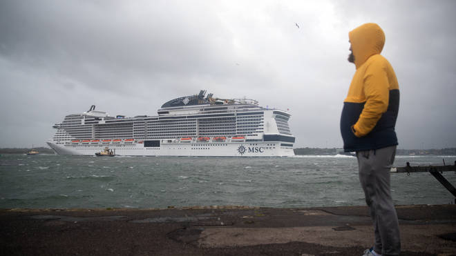 A person looks out to sea as the cruise ship MSC Virtuosa departs Southampton