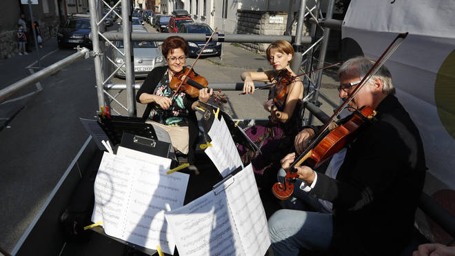 Members of the Budapest Festival Orchestra play music on the back of a truck