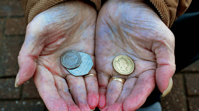 An elderly person holding a few coins