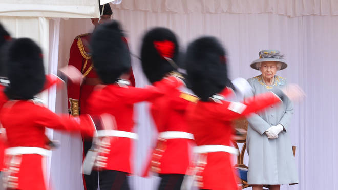 The Queen looks on as Guardsmen perform a mini Trooping the Colour