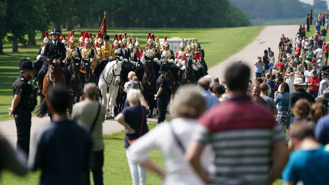 Members of the Household Cavalry make their way down the Long Walk towards Windsor Castle