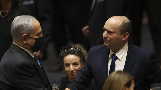 Israel PoliticsIsrael's new prime minister Naftali Bennett shakes hands with outgoing prime minister Benjamin Netanyahu during a Knesset session in Jerusalem (Ariel Schalit/AP)