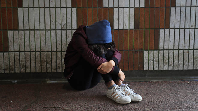 Picture posed by a model of a teenage girl sitting alone
