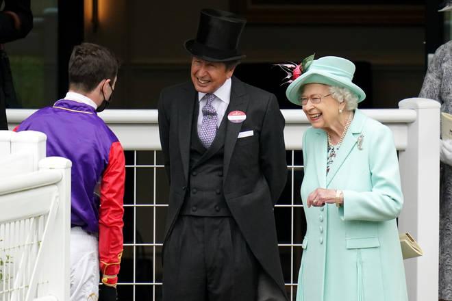 Queen Elizabeth II and racing manager John Warren (centre) speak with jockey Oisin Murphy