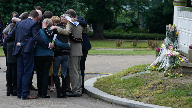 The families of the three victims of the terror attack at Forbury Gardens hug each other