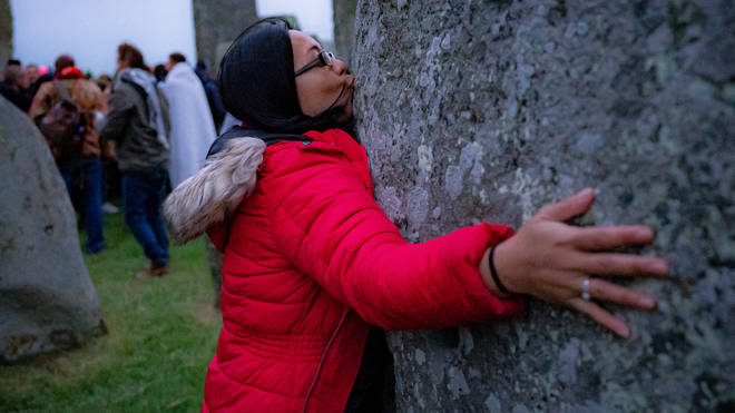 A woman kisses a stone