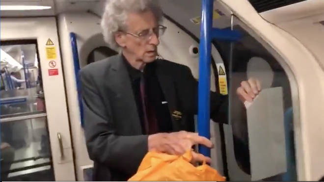 The footage shows Piers Corbyn removing the stickers and putting them into an orange carrier bag