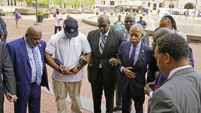 The Rev. Al Sharpton, right, with hand on coat, along with family members of George Floyd leads a prayer before entering the Hennepin County Government Center for the sentencing of former Minneapolis police officer Derek Chauvin,