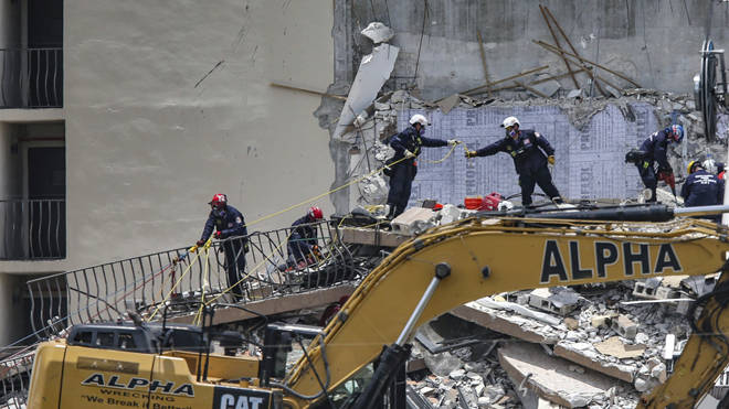Rescuers scour the rubble of the apartment building