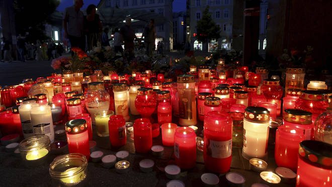 Flowers and candles in front of a closed and cordoned off department store in the city centre of Wuerzburg, Germany (Karl-Josef Hildenbrand/AP)