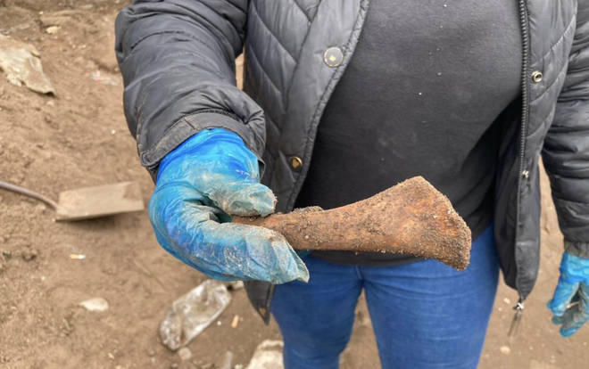 A volunteer shows an item that was found during the digging