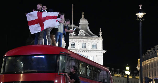 Fans celebrate on top of a bus in central London.