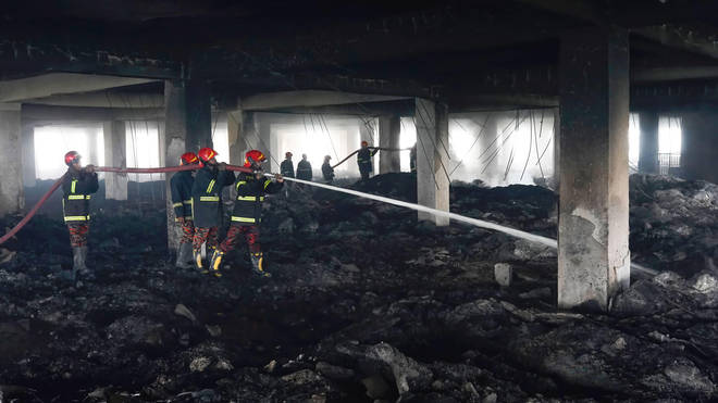 Firefighters at the site of the blaze where 52 died
