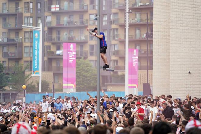 One fan climbs a lamppost outside Wembley