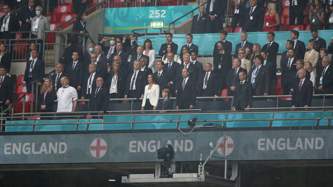 George, William and Kate stand for the national anthem