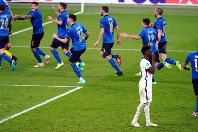 Bukayo Saka stands dejected after missing from the penalty spot