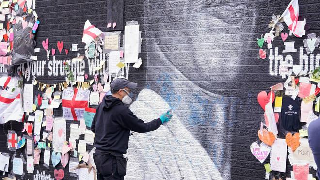 Street artist Akse P19 repairs the mural of Marcus Rashford