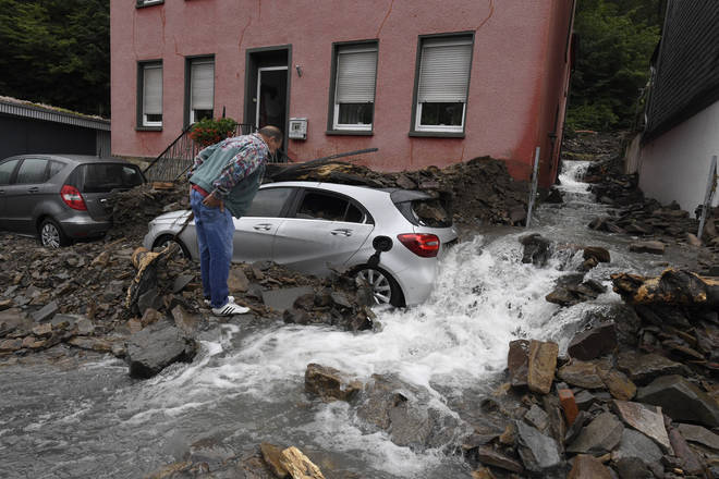 A resident looks at the damage caused by the flooding of the Nahma in Hagen, North Rhine-Westphalia. Heavy rain turned the small river into a raging torrent.