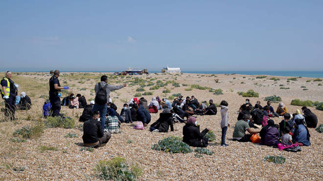 Migrants sit on the beach after arriving on a small boat at Dungeness in Kent