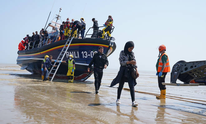 A group of people come ashore at Dungeness in Kent