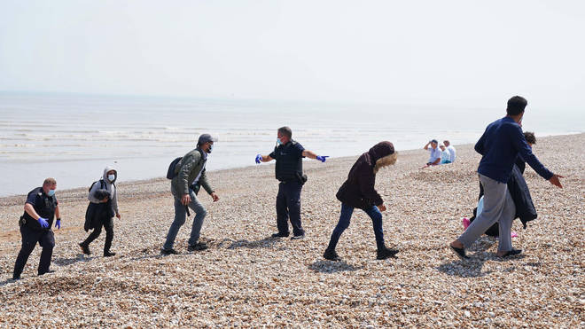 A group of people believed to be migrants being led up a beach in Kent