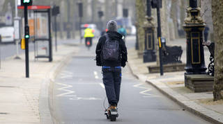 File photo of a man riding an e-scooter along London's Victoria Embankment